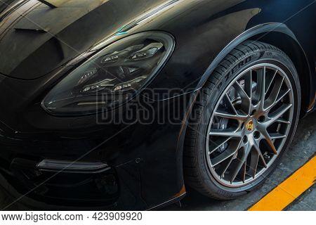 Bangkok, Thailand - 06 Jun 2021 : Close-up Of Headlights, Wheel, And Rim Of Black Porsche Sports Car