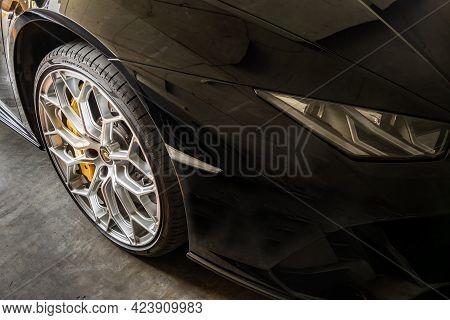 Bangkok, Thailand - 06 Jun 2021 : Close-up Of Headlights, Wheel, And Rim Of Black Lamborghini Sports