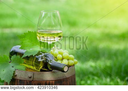 White wine bottle, glass and grape on old wine barrel with copy space
