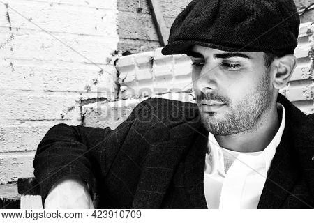 Handsome Latino Gangster Dressed In Shirt And Jacket With Flat Cap Sitting In Front Of White Brick W