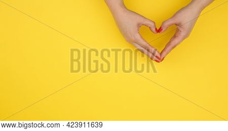 Two Female Hands Folded In The Shape Of A Heart On A Yellow Background. Gratitude And Kindness Conce