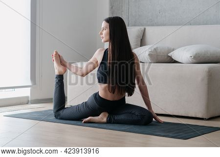Beautiful Fit Young Woman In Sport Clothes Doing One Legged King Pigeon Or Mermaid Position While Pr