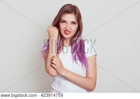 Attractive Young Girl With Lilac Hair Hurts Her Arm, Touching Pain Hand And Looking Directly At Came