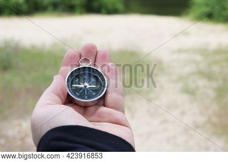 Old Classic Navigation Compass In Hand On Natural Background As Symbol Of Tourism With Compass, Trav