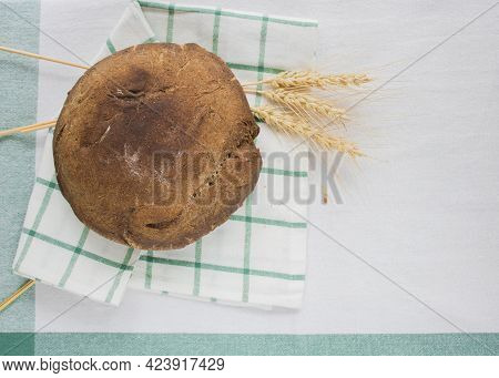 Freshly Baked Round Bread Next To The Ears Of Grain On The Linen Tablecloth. Homemade Bread. Step By