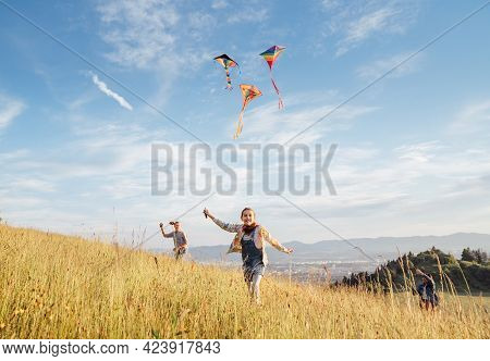 Smiling Gils And Brother Boy Running With Flying Colorful Kites On The High Grass Meadow In The Moun