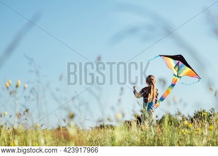9yo Smiling Girl Sitting On The Grass And Preparing Colorful Rainbow Kite Toy For Flying. Happy Chil