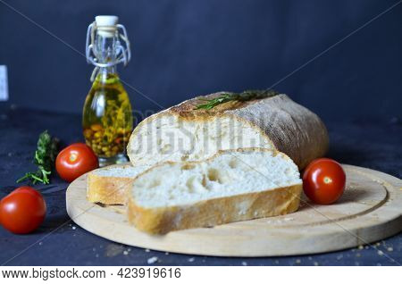 Italian Ciabatta Bread Cut In Slices On Wooden Chopping Board With Herbs, Garlic And Olives Over Dar