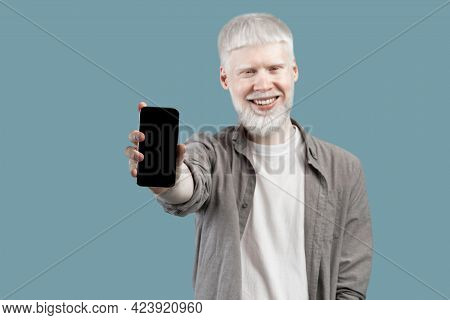 I Recommend This App. Smiling Albino Guy Holding Smartphone With Blank Screen, Isolated Over Turquoi