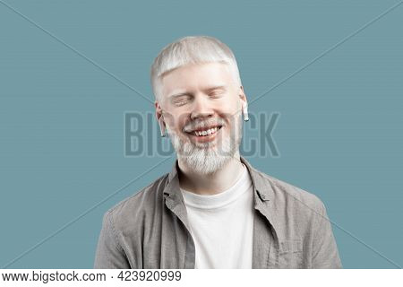 Relaxed Albino Guy Listening Music In Bluetooth Earpods, Standing With Closed Eyes Over Turquoise Ba