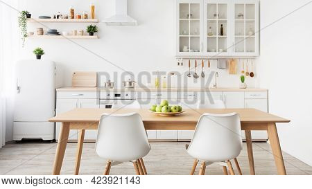 Minimalist Design Of Kitchen. Plate Of Apples On Table, Kitchenware And Utensils On Furniture, Panor