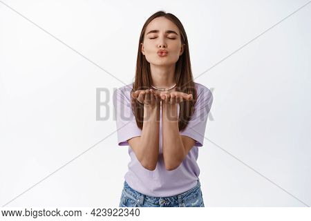 Sending You Kisses. Romantic Young Woman In Love Blowing Air Kiss At Camera With Closed Eyes, Adore