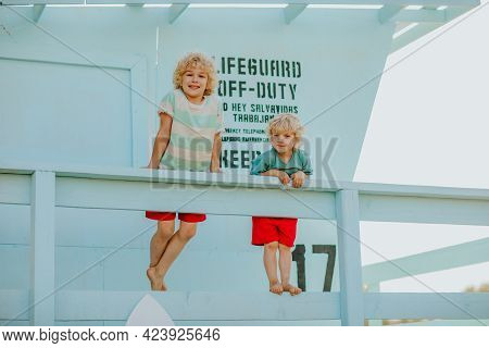Blond Curly Young Boys In Summer Clothes Posing At Blue Lifeguard Tower. Summertime.