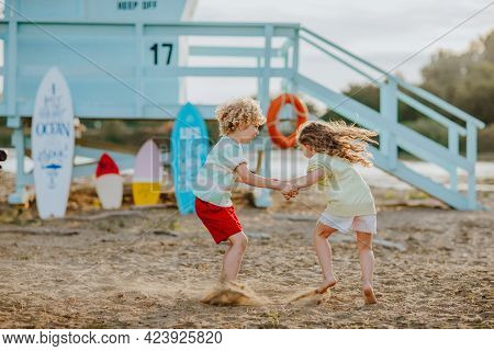 Blond Curly Young Boy And Girl In Summer Clothes Playing At The Sand Beach Against Blue Lifeguard To