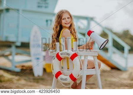 Young Pretty Curly Girl Sitting On High White Chair With Lifeline And Posing With Megaphone On The B