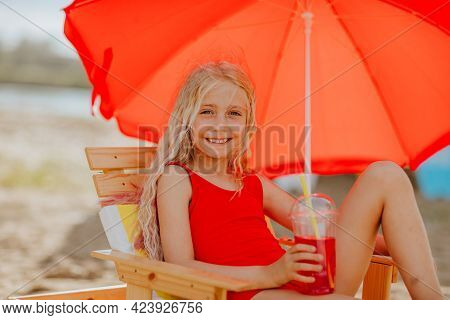 Young Pretty Girl In Summer Bikini Laying On Beach Chair With Red Umbrella And Enjoying Her Cocktail