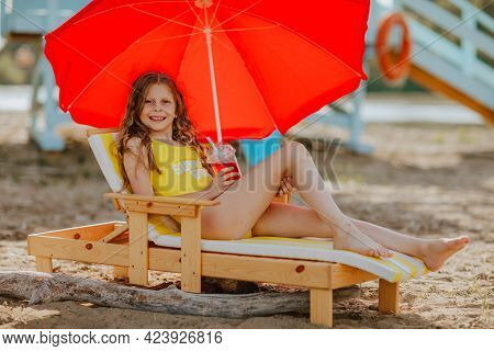 Young Pretty Girl In Yellow Summer Bikini Laying On Beach Chair With Red Umbrella And Enjoying Her C