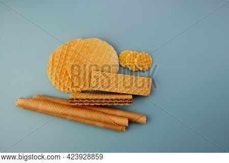 Three Types Of Waffles On A Blue Background. Round Waffles, Filled Waffles And Long Wafer Rolls.