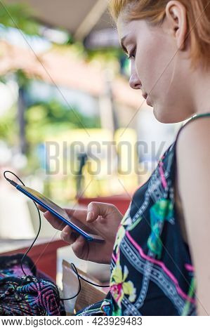 Woman Is Sitting In A Summer Cafe And Typing Something On Her Phone. Concept Of Social Networks And