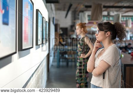 Young Woman In Modern Art Exhibition Gallery Hall Contemplating Artwork. Abstract Painting