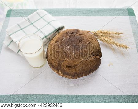 Freshly Baked Round Bread And A Glass Of Milk Next To The Ears Of Grain On The Linen Tablecloth. Hom