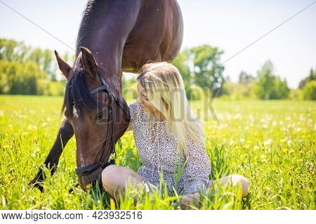 A Young Rider Woman Blonde With Long Hair In A Dress Posing With Brown Horse On A Field And Forest B