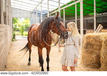 A Young Rider Woman Blonde With Long Hair In A Dress Posing With Brown Horse Inside Light Stable, Ru