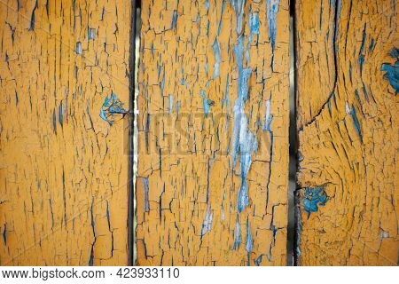 Wood Texture With Yellow Flaked Paint. Peeling Paint On Weathered Wood. Old Cracked Paint Pattern On