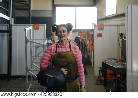 a portrait of a women welder holding a helmet and preparing for a working day in the metal industry