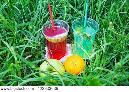 A Couple Of Glasses Of Red Drink With A Piece Of Apple, A Green Drink With A Sprig Of Mint On A Back