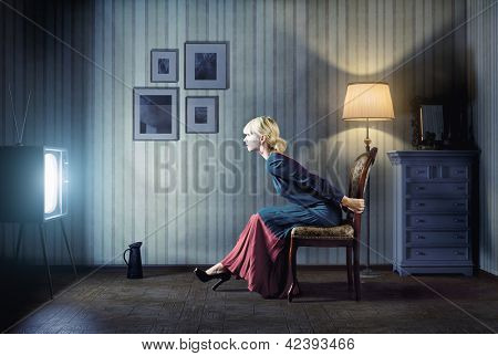Young  woman sitting on a chair in vintage interior  and watching retro tv. She is very astonished while watching tv in dark room