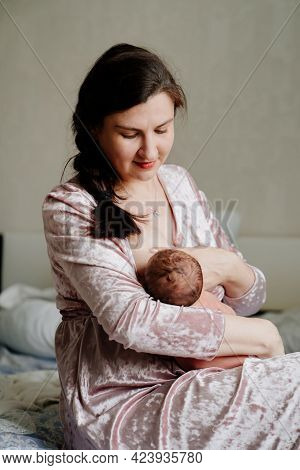 Mother Breastfeeds Newborn Baby. Naturalness And Convenience Of Breastfeeding.