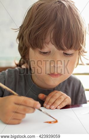 Children draw a picture in home, Boy studying paint with watercolors at school