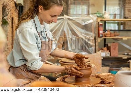 Woman Potter Working On Potter Wheel Making A Clay Pot. Master Forming The Clay With Her Hands Creat