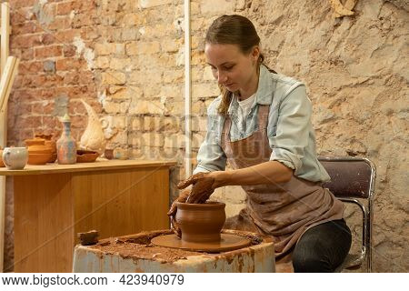 Female Potter Sculpts A Clay Pot. The Sculptor Works With Clay On A Potters Wheel And At A Table