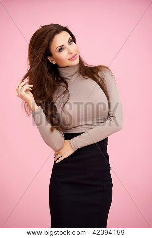Three quarter studio portrait of a beautiful stylish woman playig with her long brunette hair twiddling it in her fingers against a pink background
