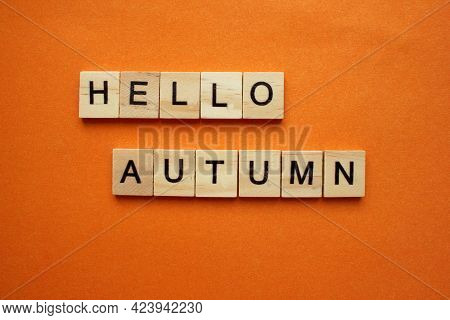 The Word Hello Autumn Is Made Of Wooden Cubes On An Orange Background. The Word Is On Top. The Conce