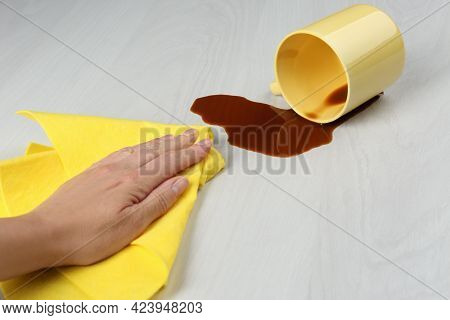 Woman Cleaning Spilled Coffee On White Wooden Table, Closeup