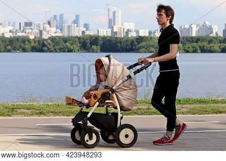 Moscow, Russia - June 2021: Young Man With Baby Pram Walking On Background Of River And Skyscrapers