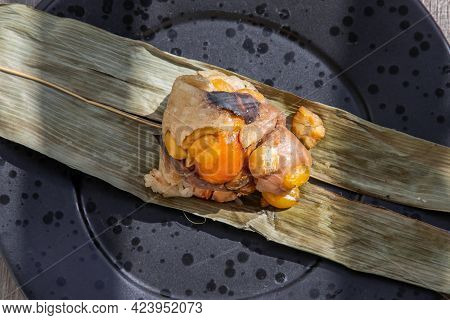 Chinese Rice Dumpling (zongzi) Shaped Pyramidal Wrapped By Leaves Ingredients On Dried Banana Leaf.
