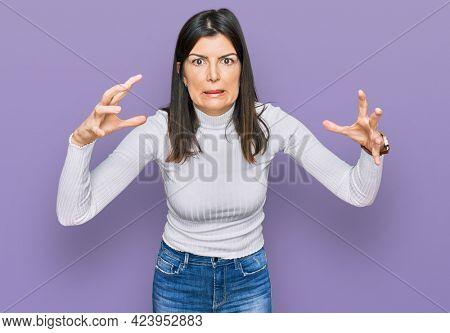 Beautiful brunette woman wearing casual clothes shouting frustrated with rage, hands trying to strangle, yelling mad