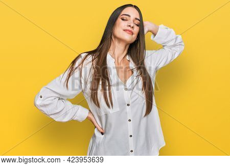 Young beautiful woman wearing casual white shirt suffering of neck ache injury, touching neck with hand, muscular pain