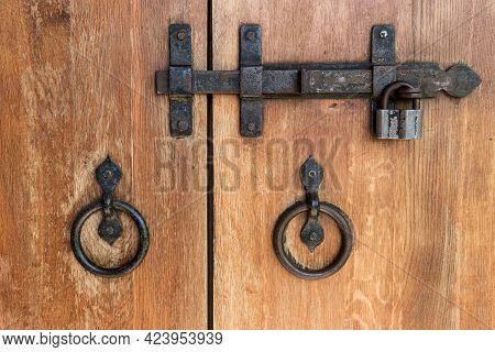 Close-up Of Wooden Doors With Wrought Iron Handles And A Deadbolt.