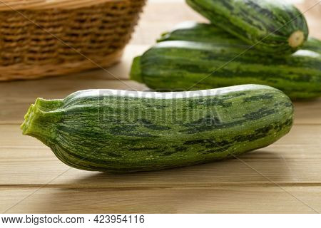 Single fresh raw green spotted courgette on a cuttingboard close up