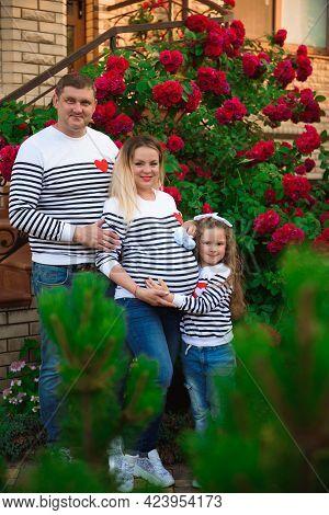 Young Pregnant Woman With Her Husband And Daughter Outdoors.
