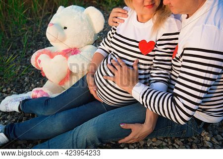 Beautiful Pregnant Woman With Her Family Sitting By The River.