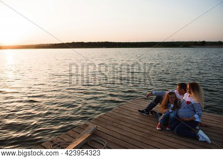 A Pregnant Mother, Her Husbant And Daughter Relaxing On The Bridge By The River