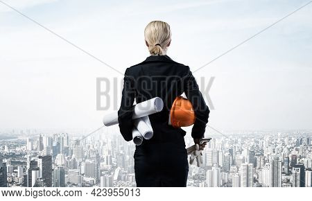 Woman Architect Standing With Construction Drawings And Hardhat. Back View Of Supervisor On Backgrou