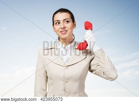 Attractive Young Woman Holding Red Retro Phone. Call Center Operator In White Business Suit Posing W