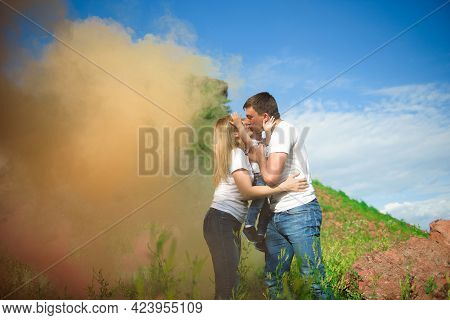 Happy Family Of Three On A Background Of Colored Smoke In Summer